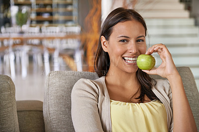 Buy stock photo Portrait of an attractive young woman eating an apple while relaxing on a sofa