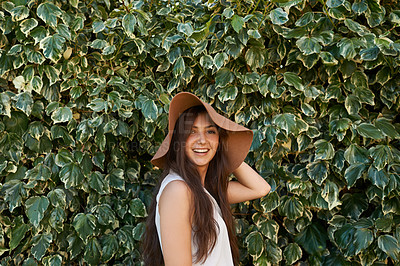 Buy stock photo Cropped portrait of a pretty teenage girl standing in front of a large hedge