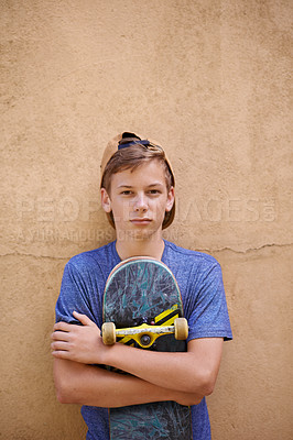 Buy stock photo Portrait of a teenage boy holding his skateboard while standing  against a wall