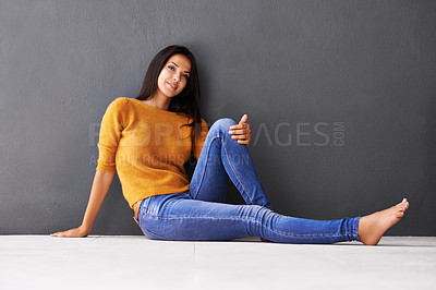 Buy stock photo An attractive young woman leaning against a gray wall while sitting on the floor