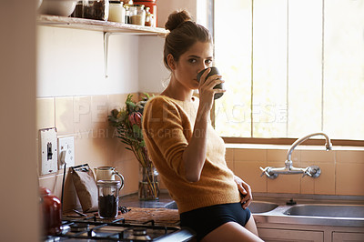 Buy stock photo A young woman casually drinking coffee while standing in her kitchen