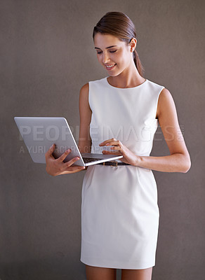 Buy stock photo Attractive businesswoman using a laptop while standing against a white background