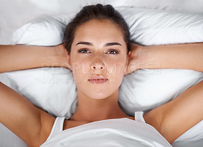 Buy stock photo Portrait of a beautiful young woman lying in bed with her hands behind her head