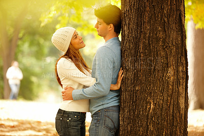 Buy stock photo Couple standing  against a tree and hugging