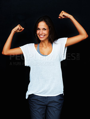Buy stock photo Woman flexing muscles against black background