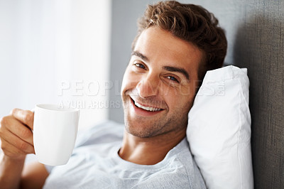 Buy stock photo Portrait of a smiling young guy enjoying a cup of coffee at home