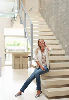 Buy stock photo Portrait of a relaxed mid adult woman sitting on stairs in a modern house