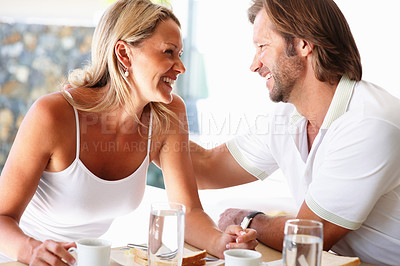 Buy stock photo Portrait of a romantic cheerful mature couple looking at each other at dining table