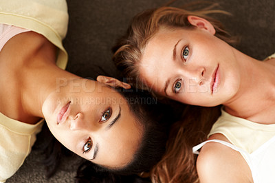 Buy stock photo Closeup portrait of beautiful young females lying head to head