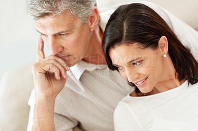 Buy stock photo Thoughtful middle aged man sitting with his beautiful wife looking away
