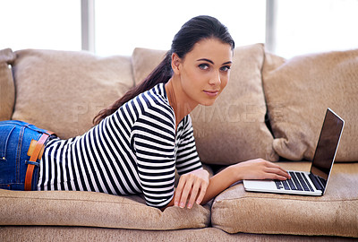 Buy stock photo Shot of a young woman sitting in her living room using a laptop