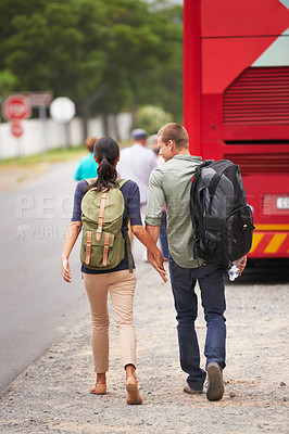 Buy stock photo Rear view shot of a travelling couple walking towards their bus