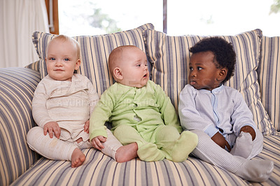 Buy stock photo Shot of three adorable babies sitting on a couch