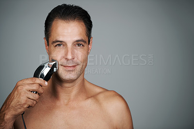 Buy stock photo Portrait of a handsome mature man shaving his face with an electric razor