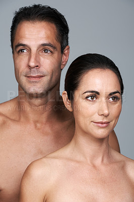 Buy stock photo Studio shot of a mature couple standing close together against a gray background