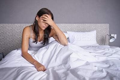 Buy stock photo Shot of an attractive young woman sitting on her bed looking unhappy