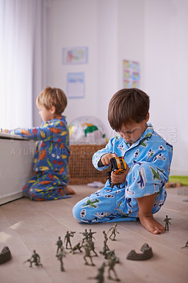 Buy stock photo Two brothers sitting on the floor playing separately with their toys