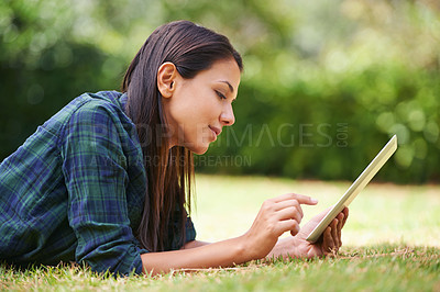 Buy stock photo Shot of an attractive young woman lying on the grass using a digital tablet