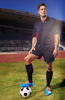 Buy stock photo Shot of a young footballer standing on a field with a ball under his foot