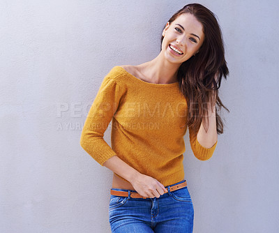 Buy stock photo Portrait of a beautiful young woman laughing while standing against a gray background