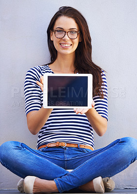 Buy stock photo Shot of an attractive young woman holding up a digital tablet with a blank screen