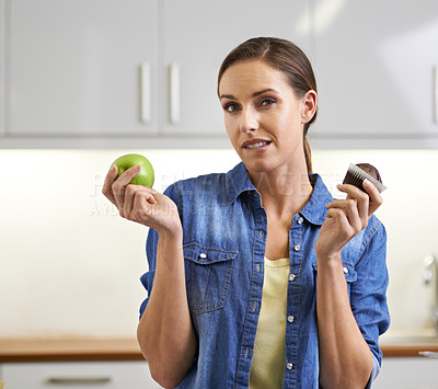 Buy stock photo A woman trying to choose between a cupcake and an apple