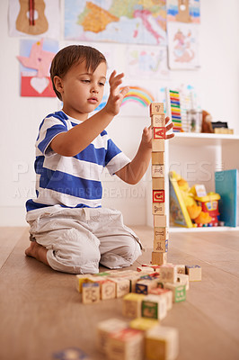 Buy stock photo Shot of a cute little boy boy playing with building blocks in his room