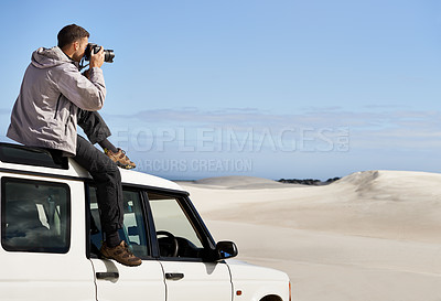 Buy stock photo Shot of a young man taking a picture from the roof of his car