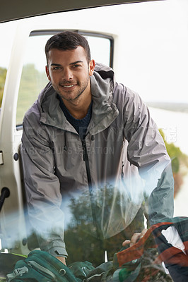Buy stock photo Portrait of a handsome young man getting gear out of the back of a car