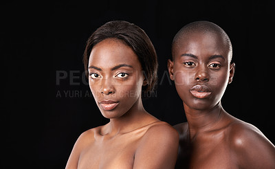 Buy stock photo Two beautiful african women posing in front of a black background with bare shoulders