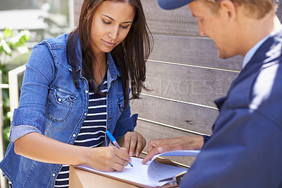 Buy stock photo Shot of a young delivery man delivering a package to a young woman