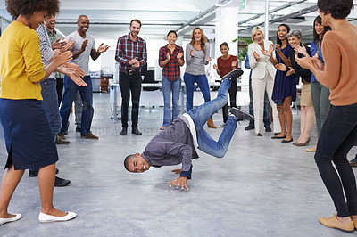 Buy stock photo Shot of a young man breakdancing in a circle of colleagues