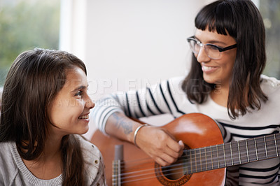 Buy stock photo Shot of an attractive woman playing the guitar with her daughter