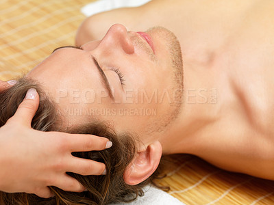 Buy stock photo Close up portrait of a young man getting a facial massage on his holiday at the day spa.