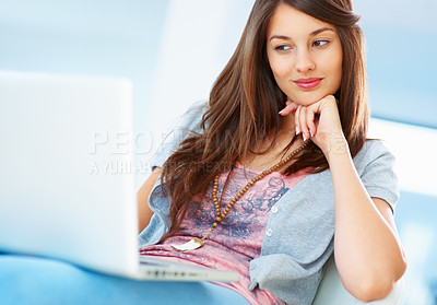 Buy stock photo Young girl relaxing while browsing the internet on her laptop at home - copyspace