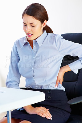 Buy stock photo Young business woman sitting on chair and holding her lower back in pain