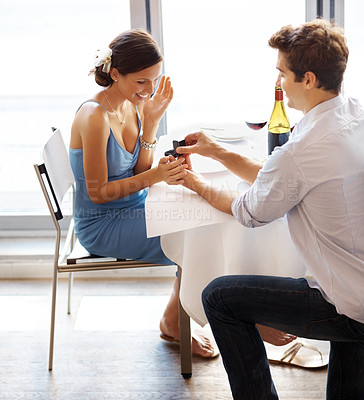 Buy stock photo Happy young man making a proposal giving engagement ring to his fiancee in a restaurant