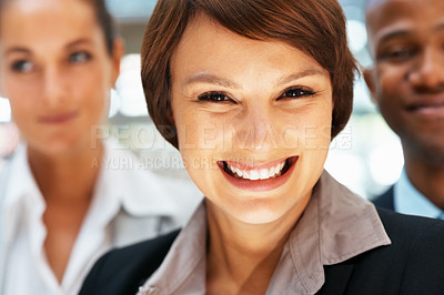 Buy stock photo Closeup of happy female executive with colleagues in background