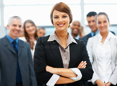 Buy stock photo Focus on female executive with colleagues in distance