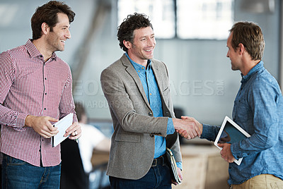Buy stock photo Shot of two coworkers shaking hands in an office