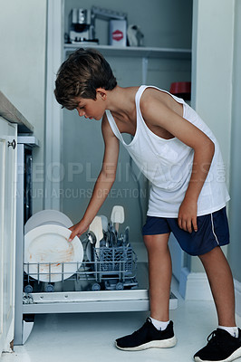 Buy stock photo Shot of a young boy loading a dishwasher at home