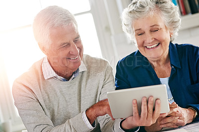 Buy stock photo Cropped shot of a senior couple using a digital tablet together at home