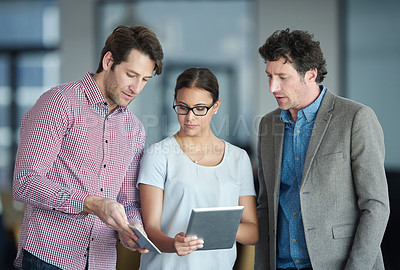 Buy stock photo Shot of a group of colleagues talking together over a digital tablet while standing in an office