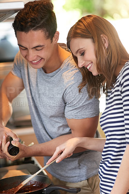 Buy stock photo Shot of a happy young couple cooking a meal together in their kitchen