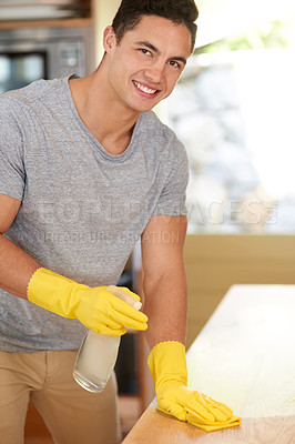 Buy stock photo Portrait of a happy young man cleaning his kitchen