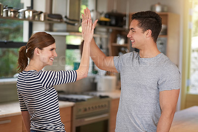 Buy stock photo Shot of a happy young couple high-fiving in their kitchen at home