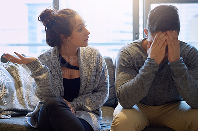 Buy stock photo Shot of a young woman scolding her boyfriend in their home