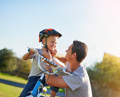 Buy stock photo Shot of a father putting a helmet on his son while teaching him how to ride a bicycle in the park