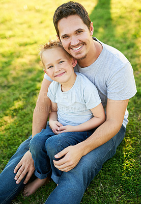 Buy stock photo Portrait of a smiling father and his little son sitting on the grass in a park