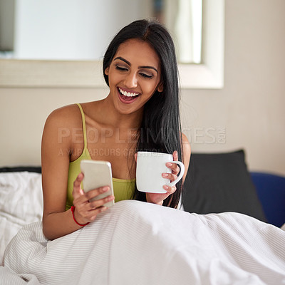 Buy stock photo Shot of a relaxed young woman drinking coffee and using her phone in bed